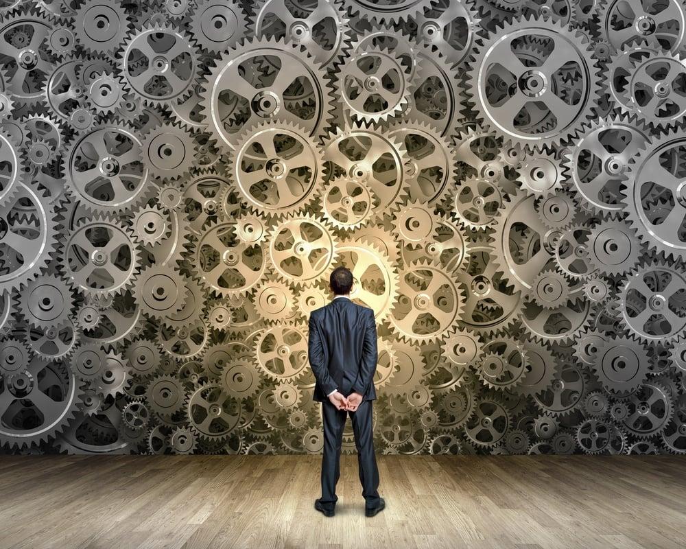 Back view of businessman looking at mechanism of cogwheels.jpeg