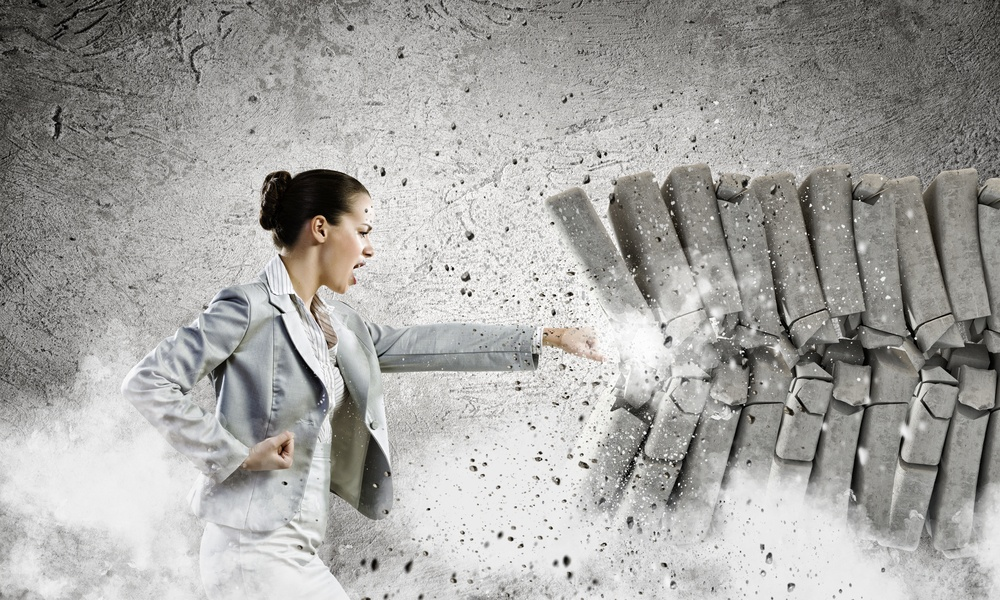 Image of businesswoman breaking bricks with hand.jpeg