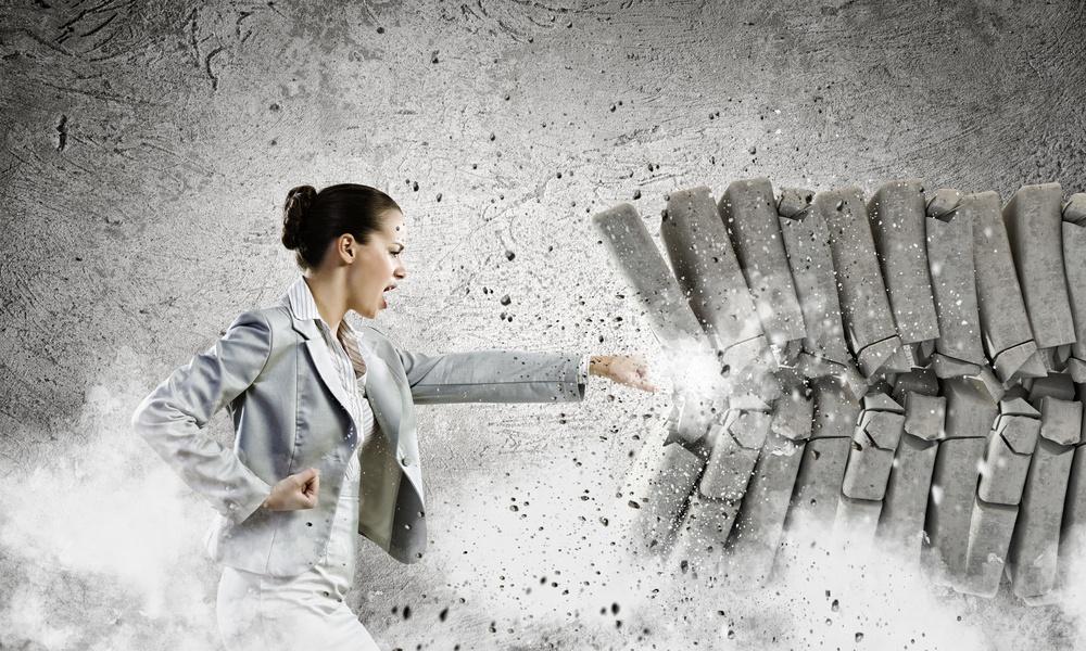 Image of businesswoman breaking bricks with hand.jpeg