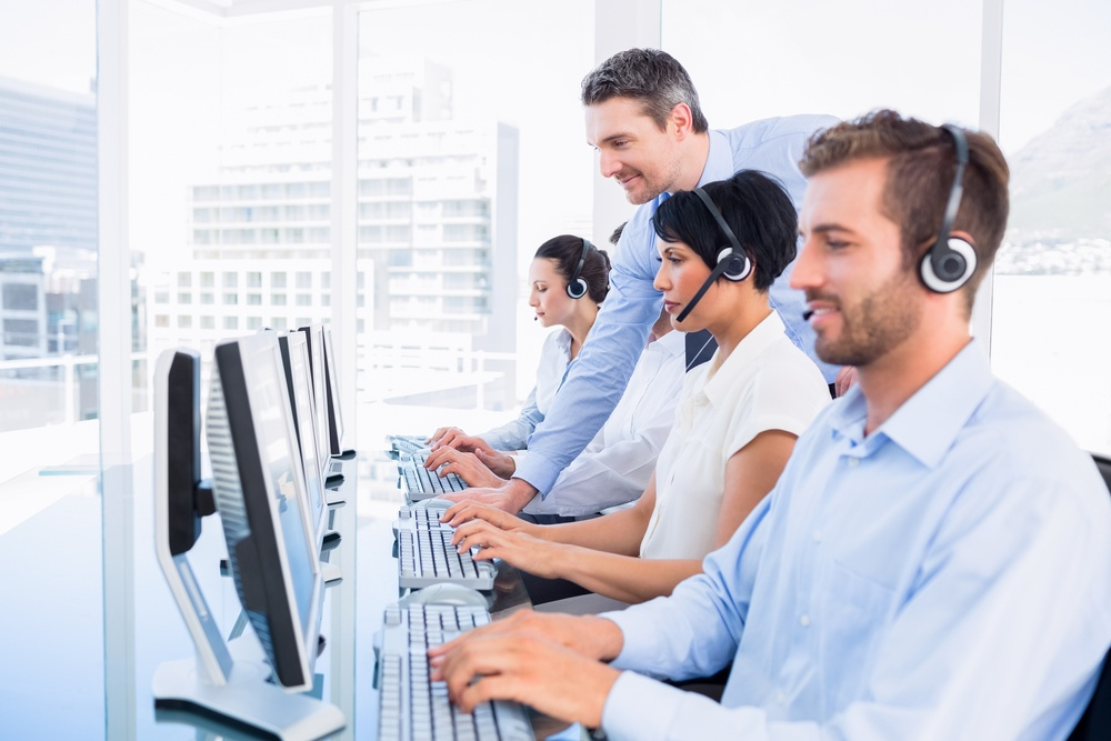 Side view of manager and executives with headsets using computers in the office.jpeg