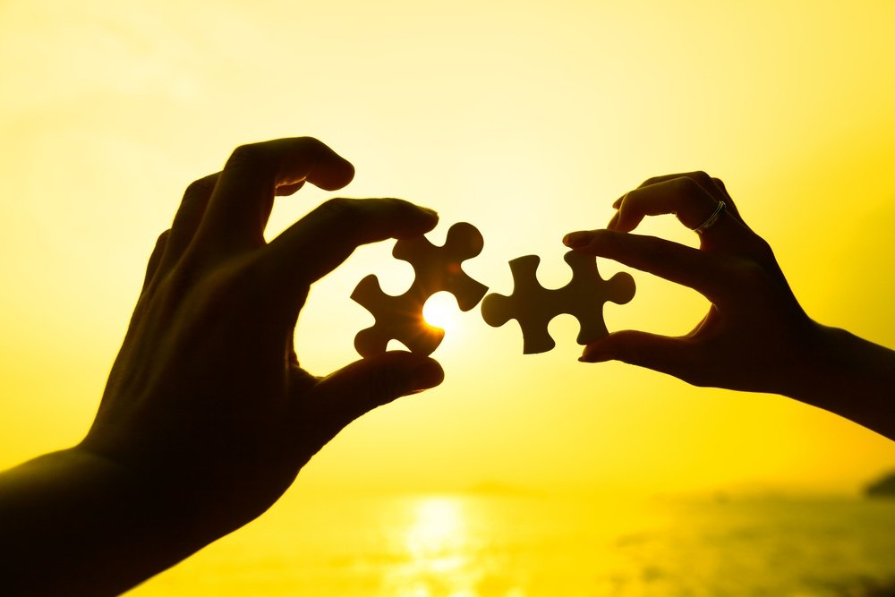 Two hands trying to connect puzzle pieces with sunset background.jpeg