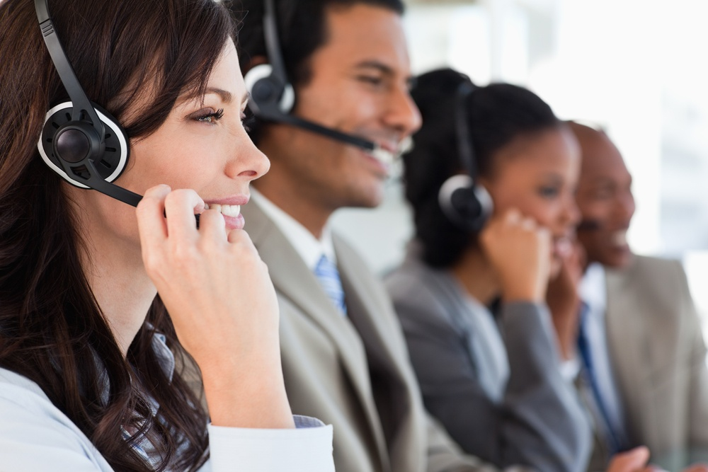 Young employee working with a headset and accompanied by her team.jpeg